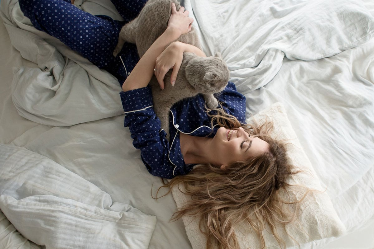 Beautiful young girl in pajamas hugs her cat lying in bed, top view