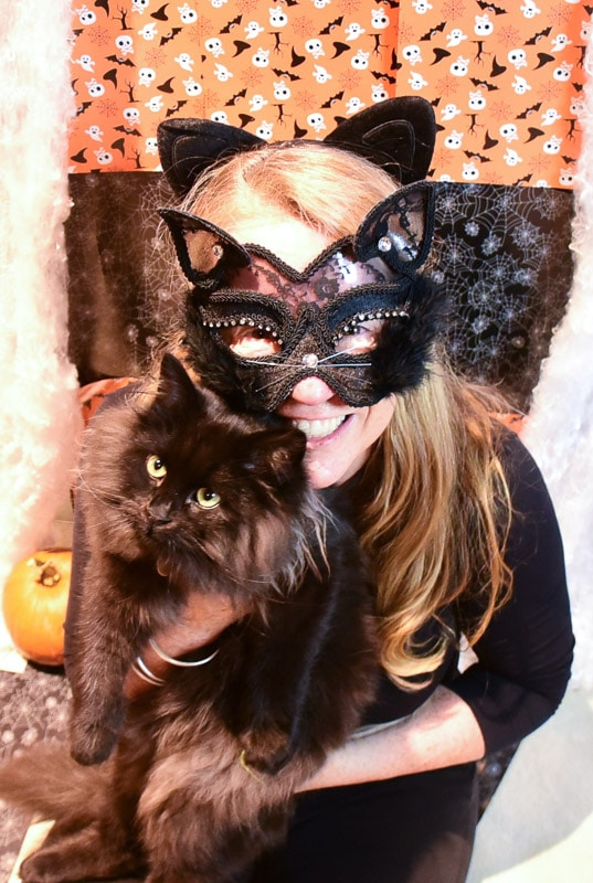 woman dressed as cat with black cat