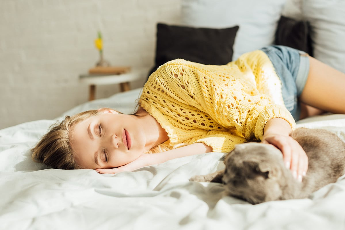 woman asleep on bed with arm reached out to cat