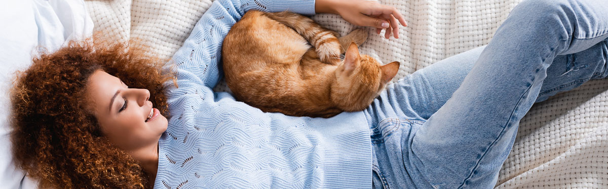 woman lying on bed with ginger cat curled up under her arm