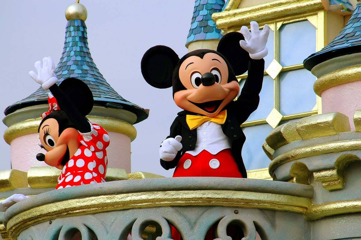 mickey and minnie mouse waving on a balcony