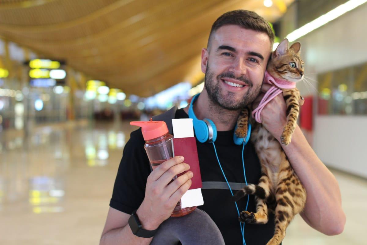 man cuddling cat in airport