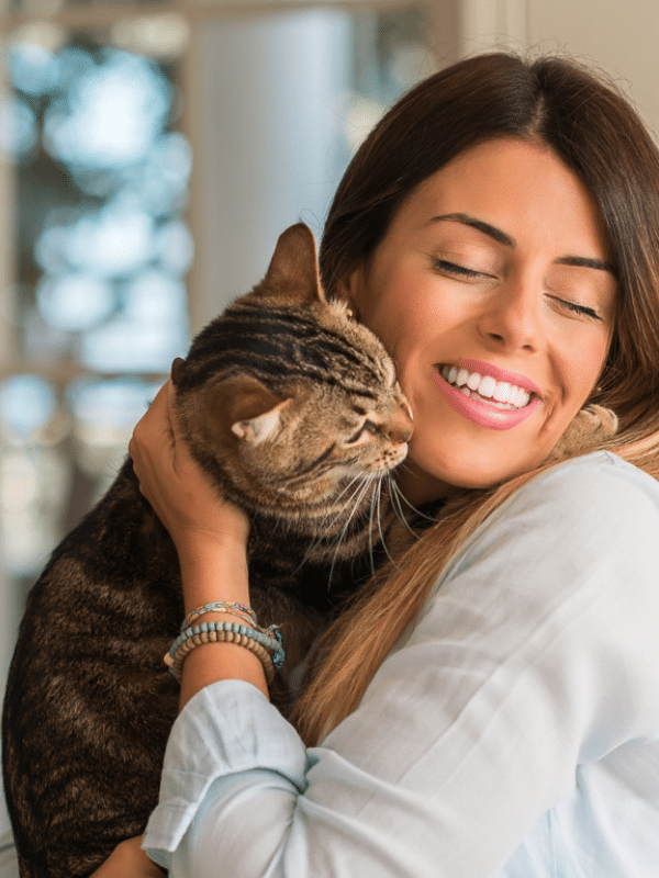 woman with brown hair cuddling tabby cat