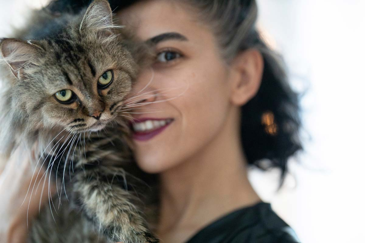 woman snuggles with tabby cat