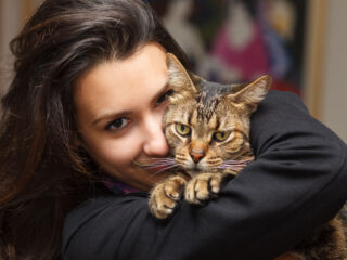 woman cuddles tabby cat